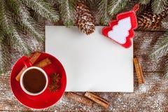 Julbaner med det gröna trädet, kottar, röd kopp med varm choklad, filtgarneringar, kanel på träbakgrund Royaltyfria Foton
