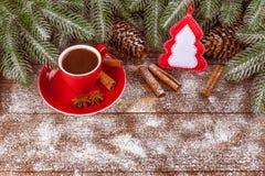 Julbaner med det gröna trädet, kottar, röd kopp med varm choklad, filtgarneringar, kanel på träbakgrund Arkivfoton
