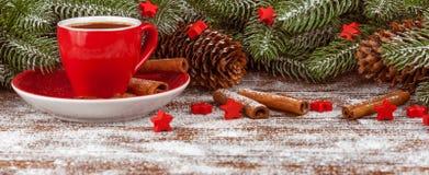 Julbaner med det gröna trädet, kottar, röd kopp med varm choklad, röd garnering, kanel på brun träbakgrund Arkivfoton