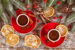 Julbaner med det gröna trädet, kottar, röda koppar med varm choklad, apelsinen och kanel på brun träbakgrund Fotografering för Bildbyråer