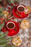 Julbaner med det gröna trädet, kottar, röda koppar med varm choklad, apelsinen och kanel på brun träbakgrund Royaltyfria Foton