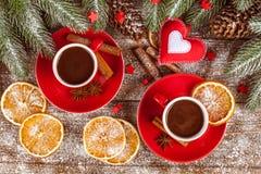 Julbaner med det gröna trädet, kottar, röda koppar med varm choklad, apelsinen och kanel på brun träbakgrund Arkivfoto