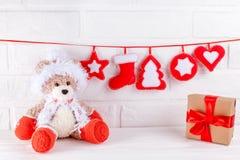 Julbaner med handgjorda filtgarneringar, leksakbjörn i jultomten dräkt, gåvaask med det röda bandet på vit bakgrund Arkivbild