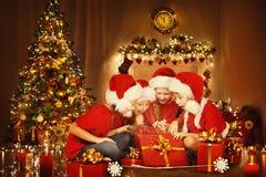 Julbarn öppnar den närvarande gåvaasken, lyckliga ungar, Xmas-träd Royaltyfri Fotografi
