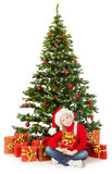 Julbarn i jultomten hatt, gåvaask under granträd royaltyfri bild
