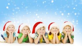Julbarn i Santa Helper Hat, små Xmas-ungar royaltyfria foton
