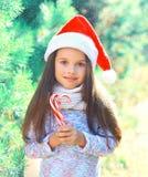 Julbarnliten flicka i santa den röda hatten med trädet för filial för söt klubbarotting det near Arkivfoto