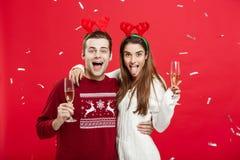 Julbegrepp - lycklig caucasian man och kvinna i renhattar som firar jul som rostar med champagneflöjter Royaltyfria Foton