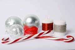 Julbegrepp - silverjulbollar, godis-pinnar och december Royaltyfri Foto