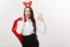 Julbegrepp - ung härlig affärskvinna i jultemat som rymmer santa den röda påsen som ger det ok tecknet Royaltyfri Foto