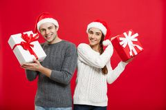 Julbegrepp - ungt attraktivt par som till varandra som ger gåvor firar i juldag Royaltyfri Fotografi