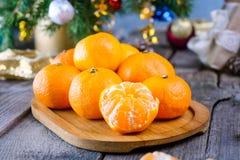 Julbegreppet med tangerin, gran förgrena sig med dekoren, gåvor och kryddor på den gamla lantliga trätabellen nytt år för bakgrun Arkivfoton