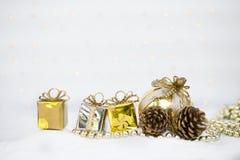 Julbegreppsbakgrund, gåvaask med sörjer kotten och den guld- bollen över suddig ljus bokeh royaltyfria foton