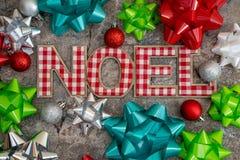 Julbegreppsbakgrund med NOEL i röd och vit pläd, prydnader och närvarande pilbågar för gåvapacke arkivfoto