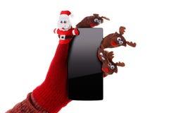 Julbegreppsleksak Santa Claus och ren med en gåva i handsmartphone Arkivfoto