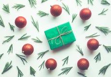 Julberömbegrepp med sörjer filial- och gåvaasken och röd bollprydnadgarnering på vit bakgrund royaltyfria bilder
