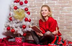Julberömbegrepp Noel och glädje Lyckligt le för kvinna nära julträd som tycker om beröm Flicka i rött fotografering för bildbyråer
