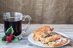 Julbild av skivor av fruktkakan på plattan med koppen kaffe Royaltyfria Bilder