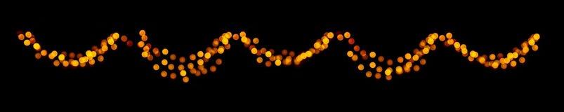 Julbokehgirland av ljusa defocused guld- cirklar på svart mörk bakgrund fotografering för bildbyråer