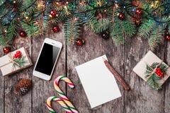 Julbokstav på träbakgrund med mobiltelefonen, gåvor, godis, granfilialer, röda garneringar arkivbilder