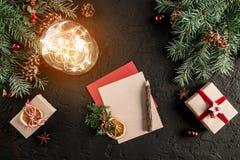 Julbokstaven för jultomten på mörk bakgrund med gåvor, granfilialer, sörjer kottar, glödande boll Tema för Xmas och för lyckligt  royaltyfri bild