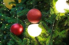 Julbollar och ljus som hänger på, sörjer trädfilialer Xmas-vinterbakgrund royaltyfri foto