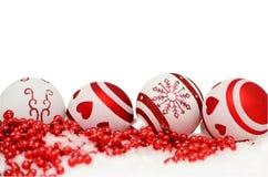 Julbollar och röd girland i snö på vit Royaltyfri Fotografi