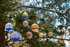 Julbollar som hänger på, sörjer filialer som täckas med snö Royaltyfri Bild