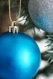 Julbollar som räcker på ett träd. Arkivbilder