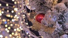 Julbollnärbild leksaker som hänger på trädet Staden dekoreras för ferien Kulör girland stock video