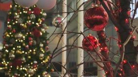 Julbollnärbild leksaker som hänger på trädet Staden dekoreras för ferien Kulör girland lager videofilmer