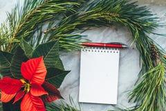 Julcloseupmodellen med julstjärnan, sörjer kransen, anteckningsbok, med kopieringsstället Hemtrevlig bakgrund arkivbild