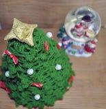 Juldekor av en boll och ett virkat gran-träd arkivbilder