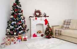 Juldekor av ljus stilfull vardagsrum med tappningsoffan, spisen, julgranen och röda stearinljus, begrepp för nytt år royaltyfri fotografi