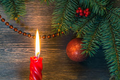 Juldekor med röda pärlor och en stearinljus Arkivbild