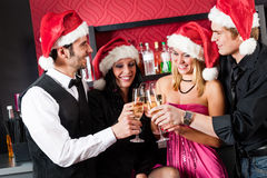 Juldeltagarevänner på stången rostar champagne Royaltyfria Bilder