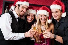 Juldeltagarevänner på stångrostat brödchampagne Arkivfoton