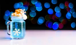 Juldrink som skjutas i ett skjutit exponeringsglas på en bokehbakgrund, julgarnering på stången, xmas-parti arkivbild