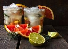 Juldrinkcoctail av nya frukter: grapefrukt limefrukt, rosmarinbegrepp av en sund drink rostig bakgrundsmetall Fotografering för Bildbyråer
