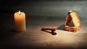 Julen bordlägger stearinljus, apelsiner och kanelbruna pinnar på trä Arkivfoto