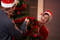julen förbunde att dekorera den lyckliga treen Arkivfoton