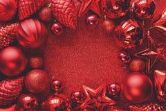julen inramniner red Julbollar, stjärnor, kottar och hjärtor på rött mousserar bakgrund Lekmanna- lägenhet Top beskådar royaltyfria bilder
