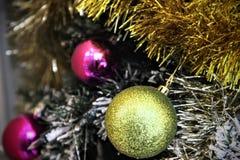 Julen klumpa ihop sig På en bakgrund av guld- guld- tinsels och den rosa bollen royaltyfri foto
