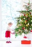 julen som dekorerar flickan, isolerade little över treewhite Royaltyfri Fotografi