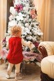 julen som dekorerar flickan, isolerade little över treewhite Arkivfoton