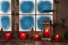 Julfönster med röda bränningstearinljus och en lykta för lodisar Royaltyfri Bild
