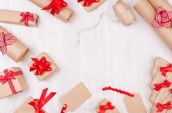 Julförberedelser - förpackande gåvaaskar i kraft papper med röda pilbågar och band, tvinnar på den vita trätabellen, ram arkivfoton