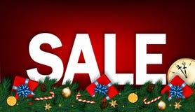 Julförsäljningsbaner med klockan, granfilialer, gåvor och godisen Arkivfoto
