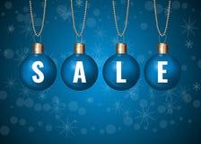 Julförsäljningstecken på blåa struntsaker över vit bakgrund Royaltyfri Foto