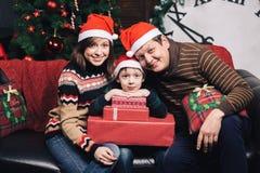 Julfamilj av tre personer i röda hattar Arkivbild